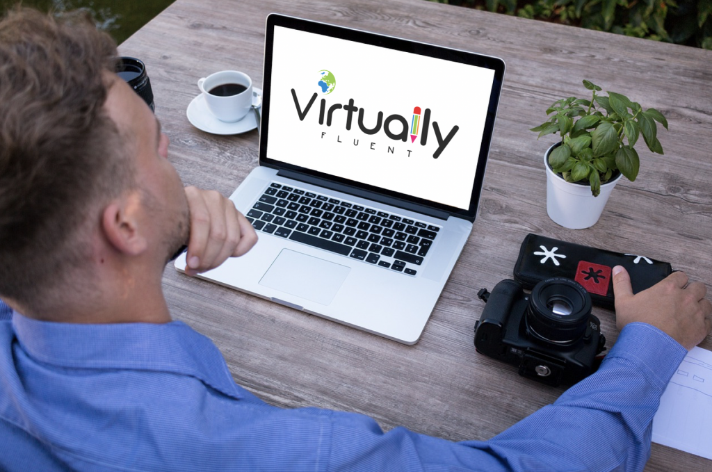 Man sitting at laptop open on Virtually Fluent page